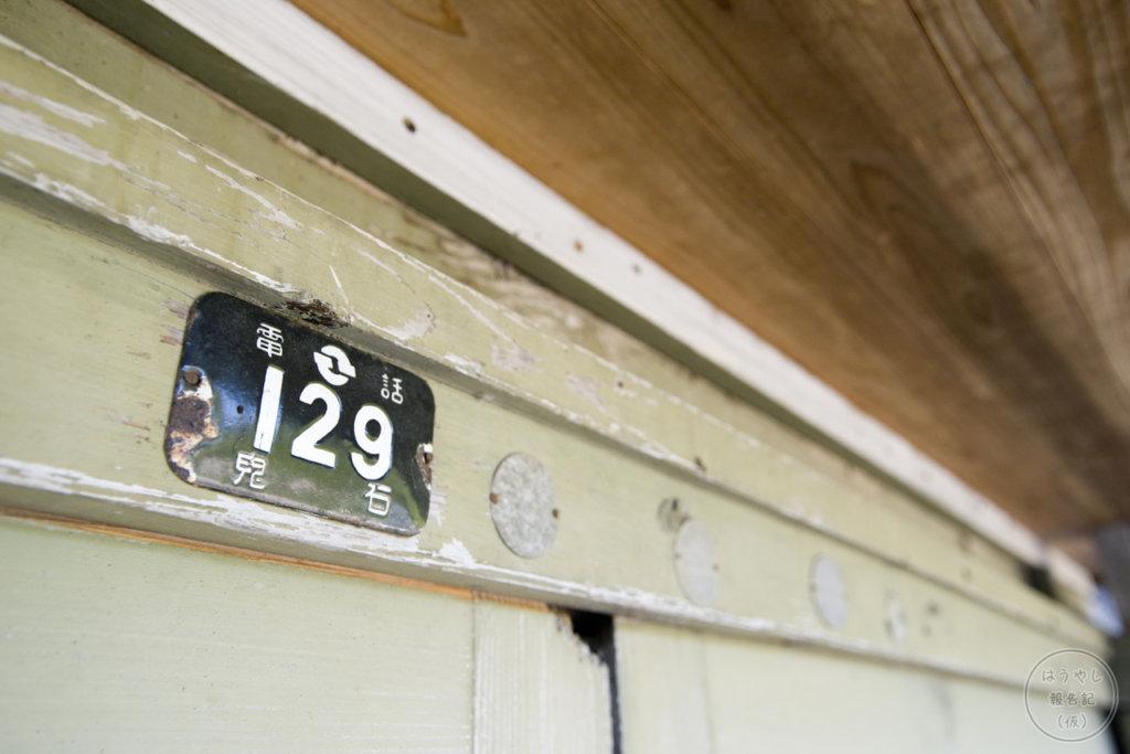 昇降口に貼られた昔の電話番号