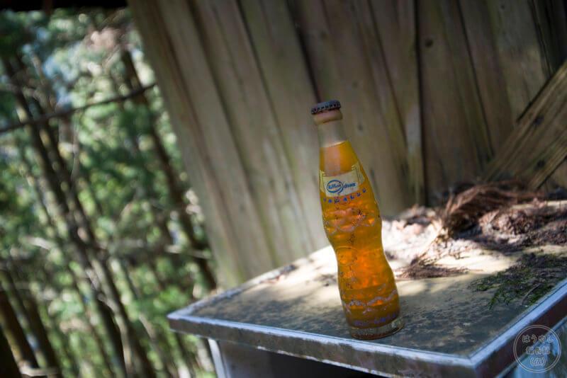 廃墟に残る未開封のビン入りオレンジジュース