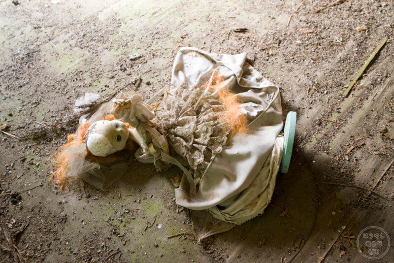 住宅廃墟の室内に転がる人形