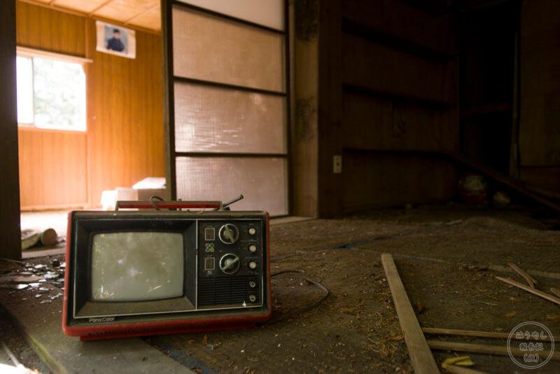 住宅廃墟に残る真っ赤なテレビ