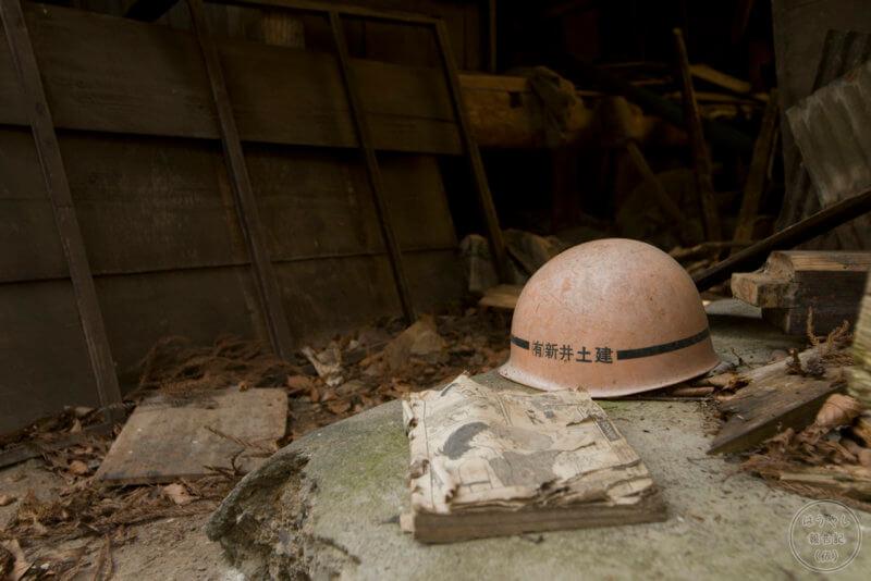 廃墟に落ちていた工事用ヘルメットと漫画