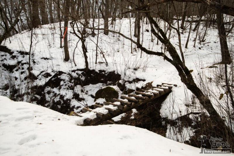雪に埋もれる丸太の橋