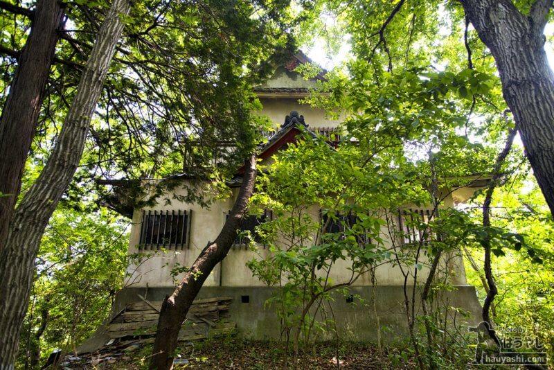 木々に覆われる模擬天守閣の裏側