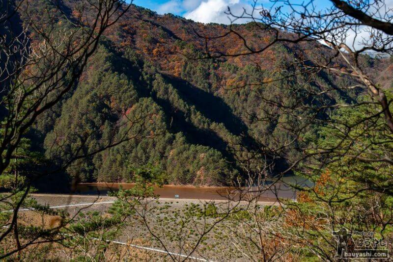 木々の間から姿を現した鉱滓ダム「簀子橋堆積場」